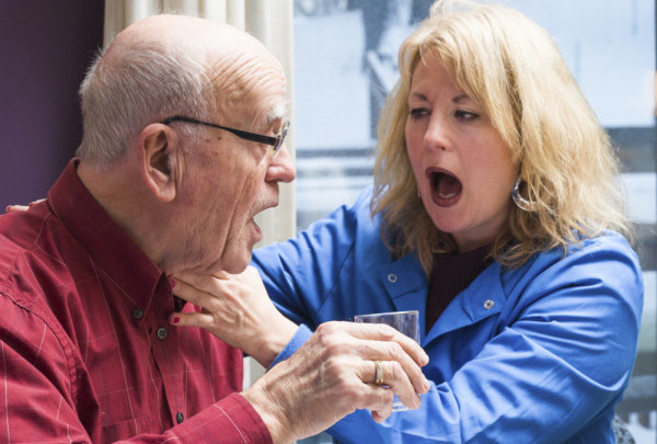 """Female speech therapist listens for wet verses dry voicing when male patient says """"ahh"""" after drinking water during a home health swallowing session addressing dysphagia"""